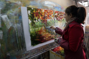 An artist in the Nan'an factory working on popular palette knife paintings popularized by Leonid Afremov